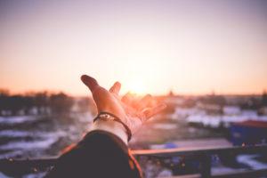 太陽に向かって伸ばす手の写真